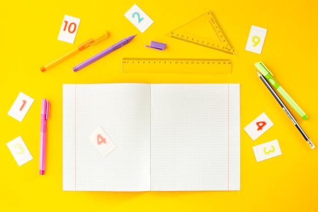 Caderno na cela entre canetas, lápis, números e réguas em um fundo amarelo