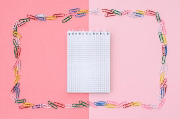 Caderno na gaiola em uma moldura de clipes de papel coloridos em um fundo duplo - rosa e coral. conceito de volta às aulas.