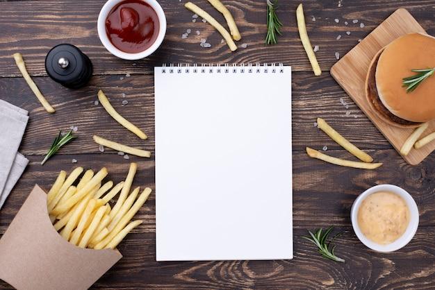 Caderno na mesa com hambúrguer e batatas fritas