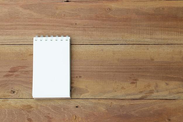 Caderno na mesa de madeira do escritório. vista do topo.
