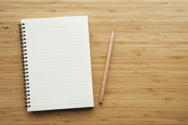 Caderno no fundo de madeira da tabela.