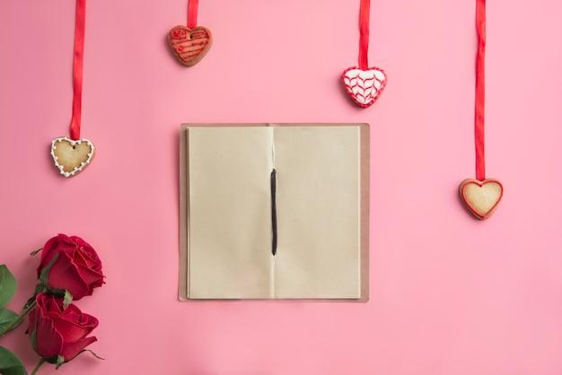 Caderno no local de trabalho de fundo rosa no dia dos namorados