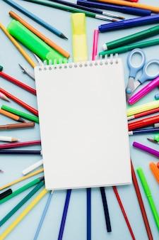 Caderno novo desobstruído em artigos de papelaria coloridos no fundo azul