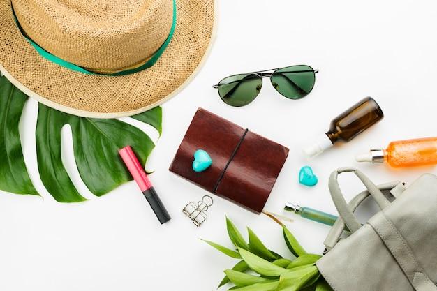 Caderno, óculos escuros, mochila cinza, cosméticos, chapéu de palha e folhas de monstera