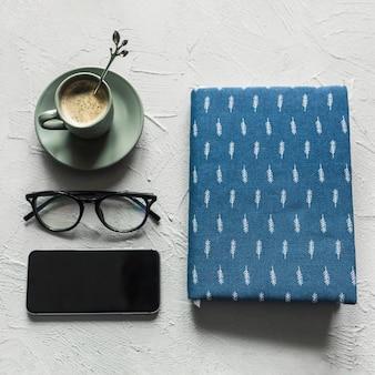 Caderno ordenadamente arranjado com óculos e café