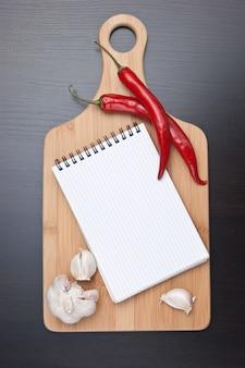 Caderno para cozinhar receitas e pimentas vermelhas na mesa da cozinha