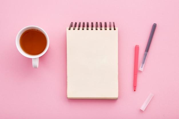 Caderno para desenhar em um fundo colorido com uma xícara de chá.