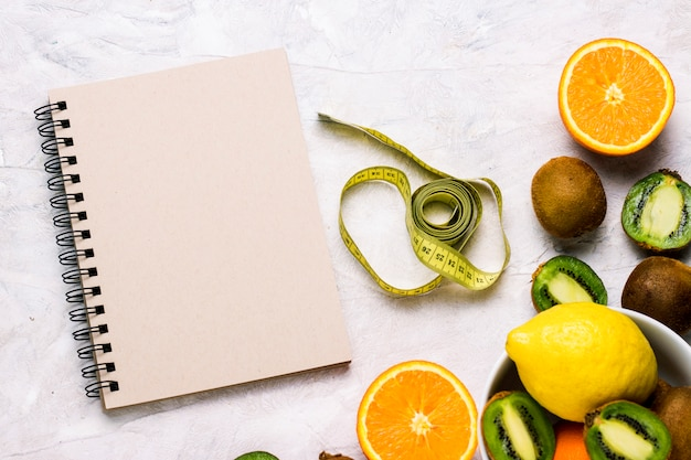 Caderno para entradas, fita métrica e frutas orgânicas, sobre um fundo de pedra claro