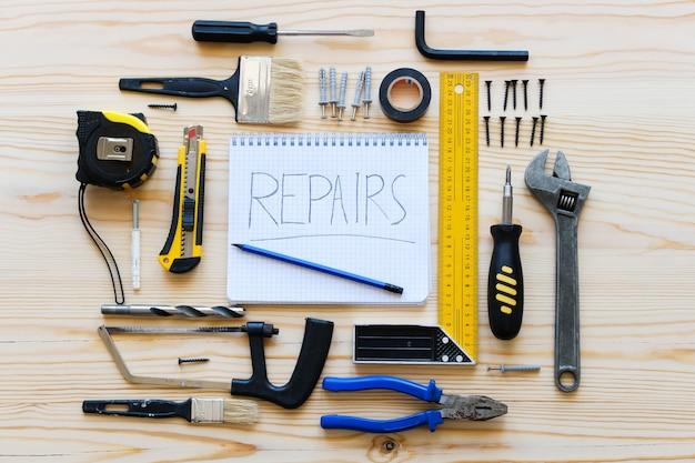 Caderno para registros e ferramentas da construção para construir uma renovação da casa ou do apartamento, em uma tabela de madeira. o local de trabalho do capataz. o tema da casa e reparação profissional, construção.