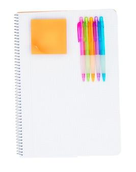 Caderno pautado com conjunto de canetas e adesivo laranja isolado