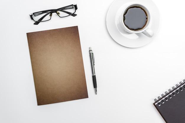 Caderno, pena e vidros da placa da vista superior no fundo branco da mesa.