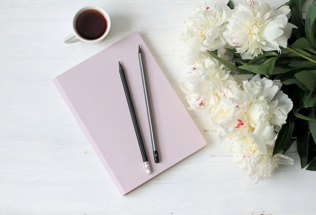 Caderno, peônias e xícara de café em madeira clara