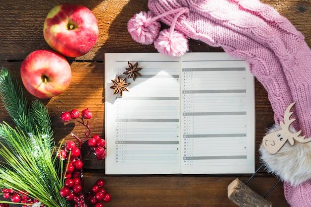 Caderno perto de meias de malha, galhos e maçãs