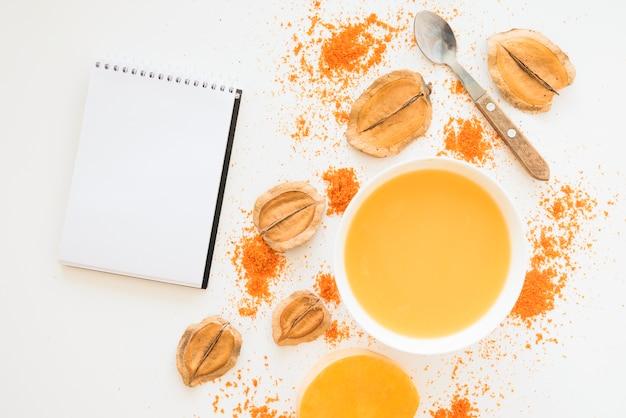 Caderno perto de pimenta de folhagem e líquido laranja