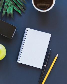 Caderno perto de xícara de café e artigos de papelaria na mesa com maçã e palmeiras