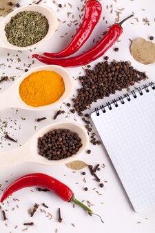 Caderno, pimenta vermelha, especiarias em colheres