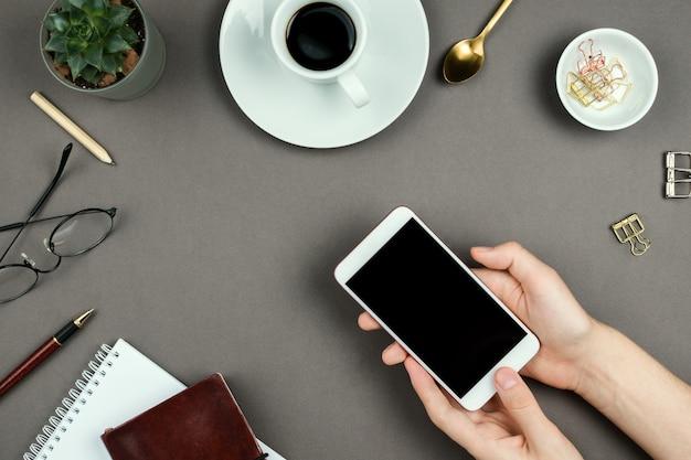 Caderno, planejador, óculos e mãos de mulher segurando um smartphone com tela preta