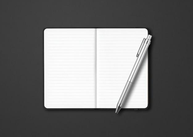Caderno preto com forro aberto com uma caneta isolada em um fundo escuro