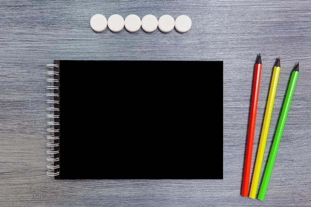Caderno preto com três lápis deita sobre a mesa. bloco de notas com lápis.