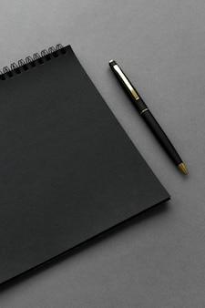 Caderno preto com uma caneta