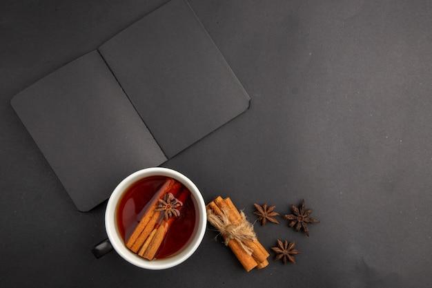 Caderno preto de vista de cima com xícara de chá aromatizado com canela e anis em paus de canela amarrados com corda na mesa escura