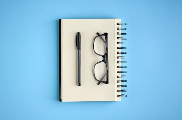 Caderno preto dos vidros, da pena e do papel na superfície azul.