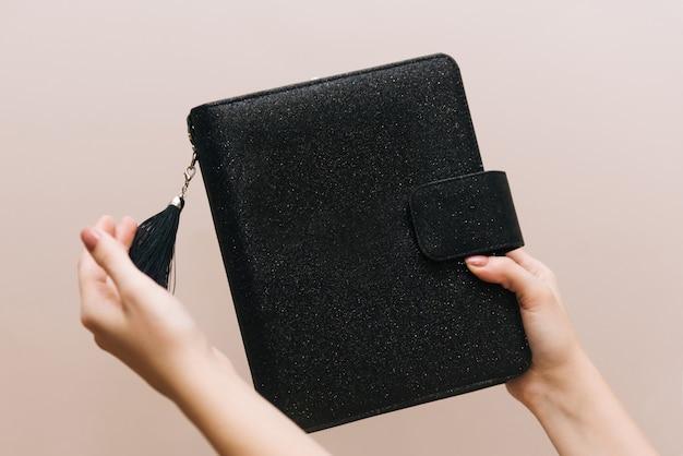 Caderno preto elegante com um pincel e um botão nas mãos da menina. espaço livre para o logotipo