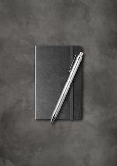 Caderno preto fechado com uma caneta. isolado em fundo escuro de concreto