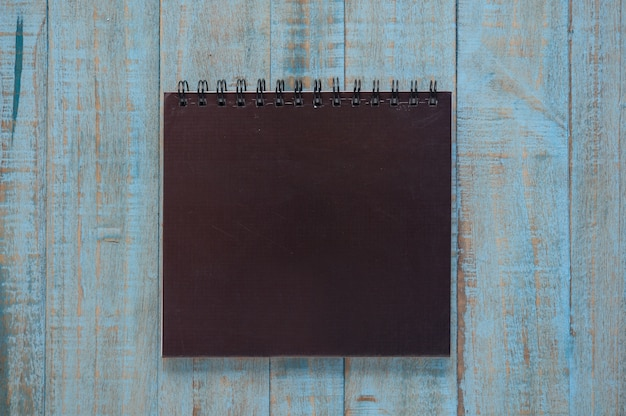 Caderno preto na mesa de madeira azul