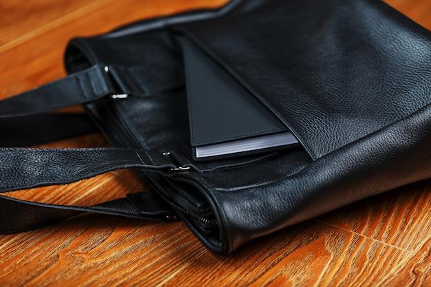 Caderno preto que espreita fora do bolso de um close de saco de couro preto, macro handmade, materiais naturais.