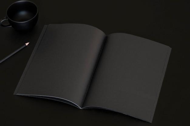 Caderno preto, xícara de café preta e lápis preto sobre fundo preto.