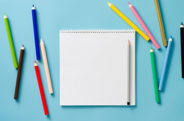 Caderno quadrado vazio e conjunto de lápis coloridos sobre fundo azul. papel em branco.