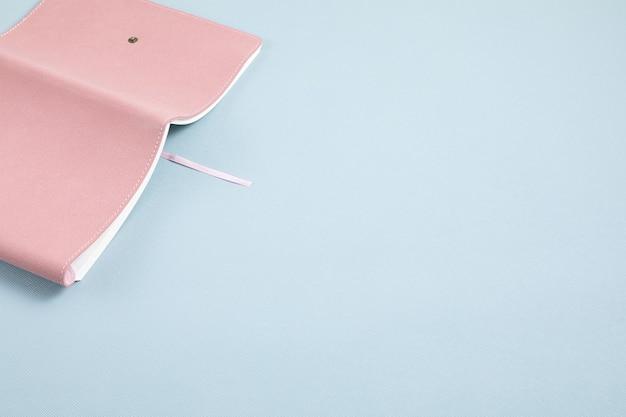 Caderno rosa aberto sobre fundo azul pastel