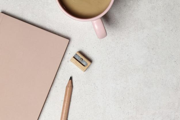 Caderno rosa com lápis de madeira, apontador, xícara de café na textura granada