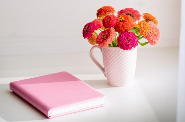 Caderno rosa e um buquê de flores.