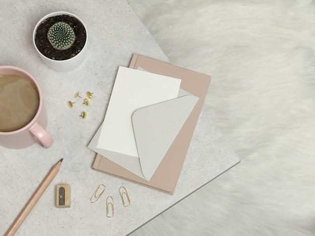 Caderno rosa, envelope prata, lápis, apontador, clipes de papel, xícara de café, cacto na mesa de granito