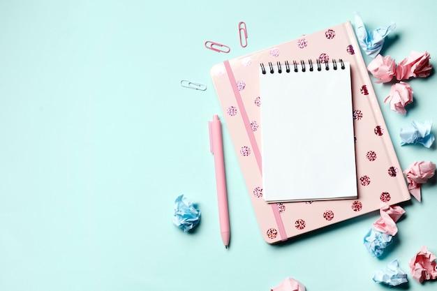 Caderno rosa sobre fundo azul com material escolar. de volta à escola. dia do professor.