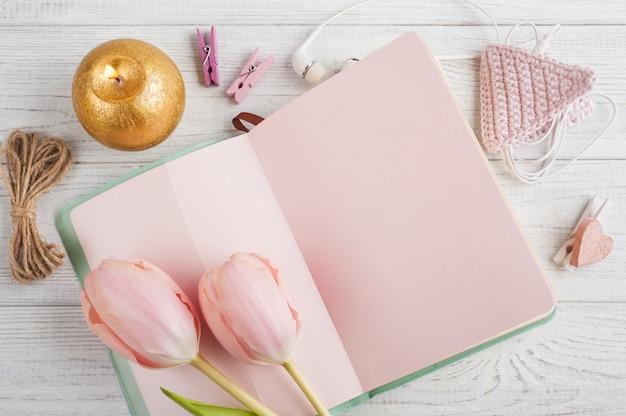 Caderno rosa, tulipas e vela acesa