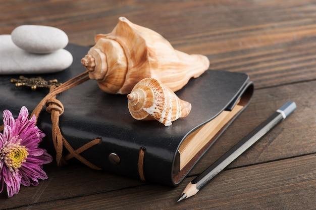 Caderno, seixos, flor, conchas.