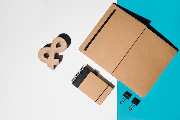 Caderno; símbolo de e comercial e bloco de notas em espiral no papel de parede duplo