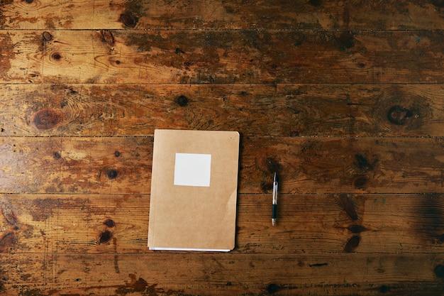 Caderno simples com capa de papel artesanal, etiqueta branca em branco e uma caneta esferográfica preta em uma mesa de madeira escovada envelhecida