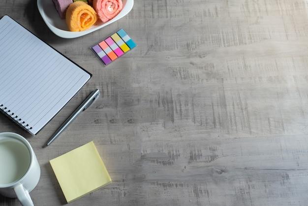 Caderno, smartphone, rolo de geleia, copo de leite, caneta em madeira, nota de papel negócios, educação, conceito e design