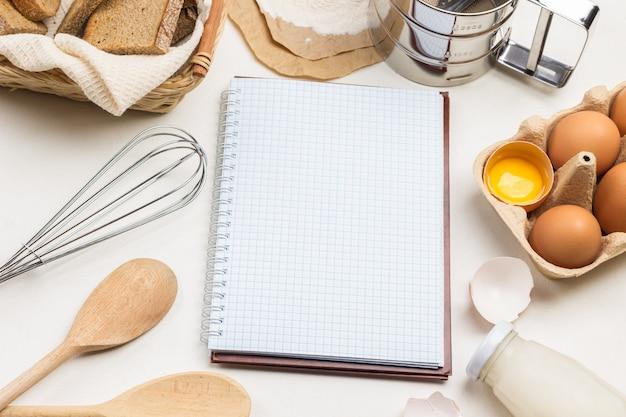 Caderno sobre molas duas colheres de madeira ovos de galinha e cascas de galinha farinha e peneira no papel