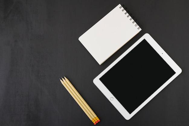 Caderno, tablete e lápis