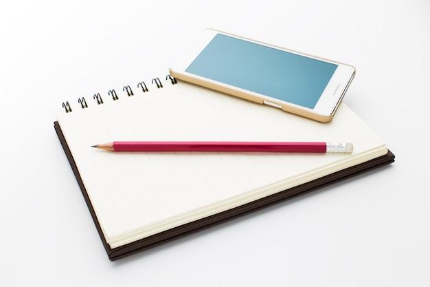 Caderno, telefone e lápis isolados no fundo branco.