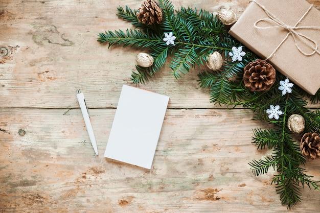 Caderno uma caneta perto de ramos de presente e coníferas