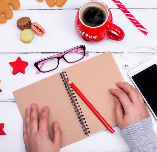 Caderno vazio aberto com um lápis vermelho