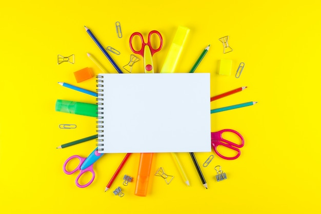 Caderno vazio aberto do modelo da escola e vários artigos de papelaria coloridos.