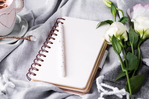 Caderno vazio aberto e buquê de eustoma de flores sobre fundo cobertor. lindo cartão em estilo vintage. postura plana.