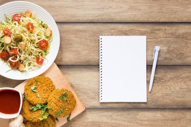 Caderno vazio ao lado de comida vegetariana